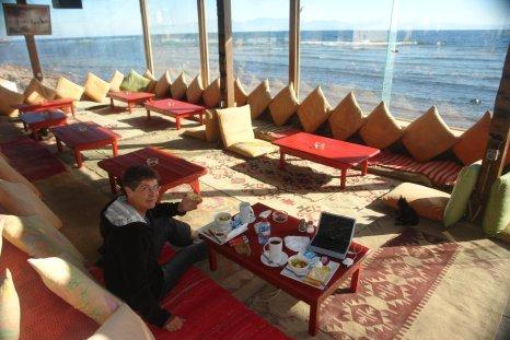 Une baba-bobo prenant son petit déjeuner dans un restaurant les pieds dans l'eau à Dahab